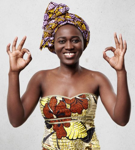 Everything is just fine! Beautiful cheerful African woman wearing bright scarf on head and elegant dress showing ok sign demonstrating her satisfaction and happiness agreeing with something.